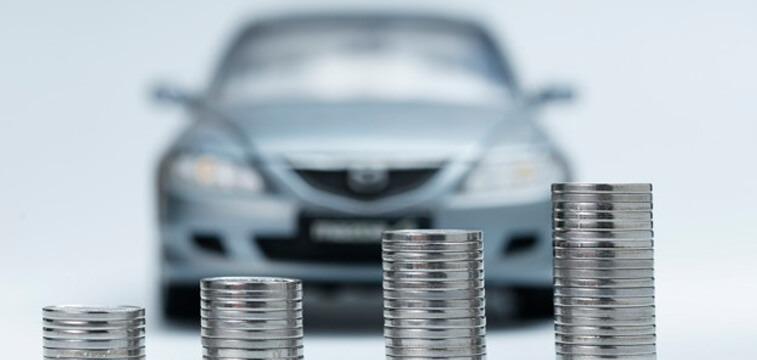 quatro fileiras de moedas empilhadas com a imagem de um carro ao fundo