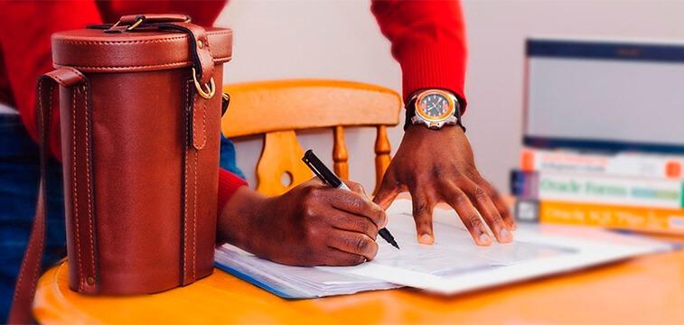homem assinando documento sobre a mesa